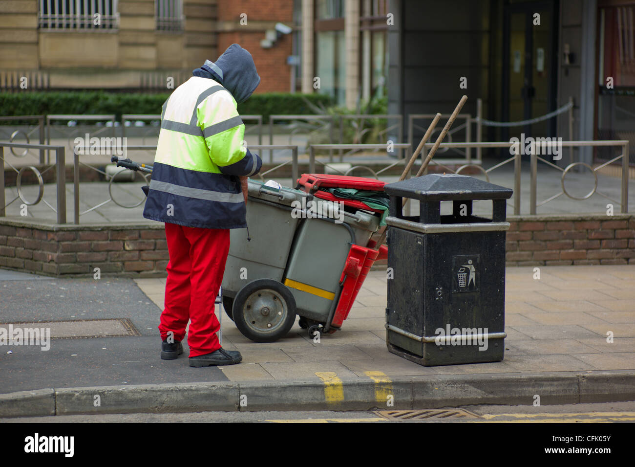 Street Cleaner pausing next to rubbish bin in Manchester City Centre, UK - Stock Image