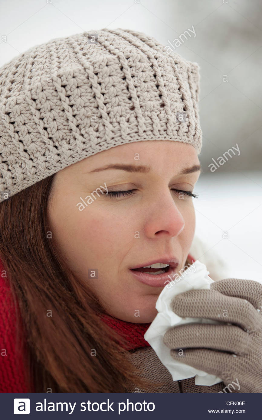 A young woman standing in the snow, sneezing - Stock Image
