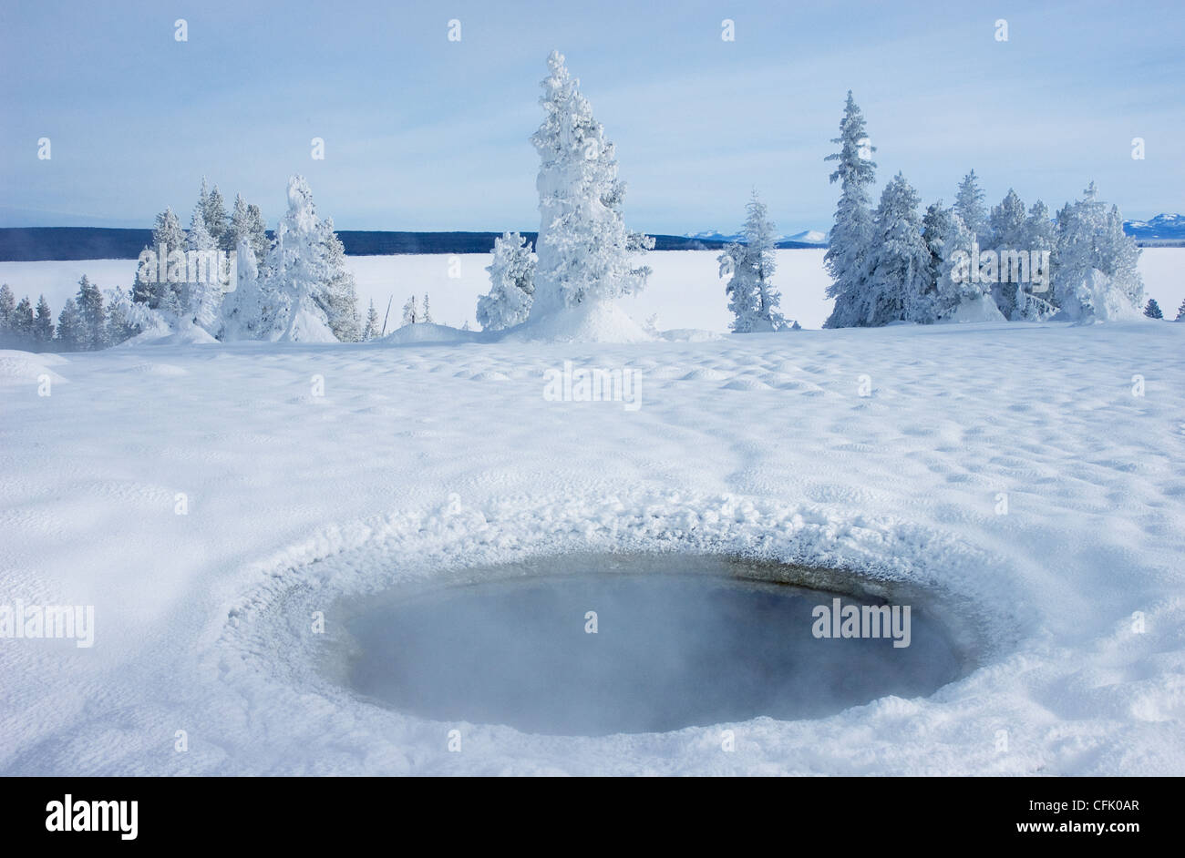 Black Pool, a geothermal hot spring, surrounded by snow in winter, at West Thumb Geyser Basin; Yellowstone National - Stock Image