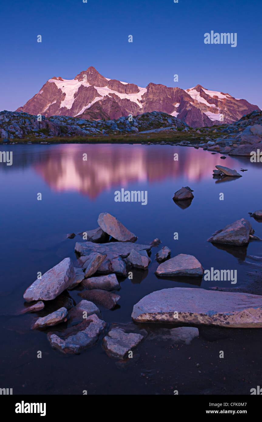 Mount Shuksan and reflection in tarn on Artist Ridge at dusk; Mount Baker-Snoqualmie National Forest, Washington. - Stock Image