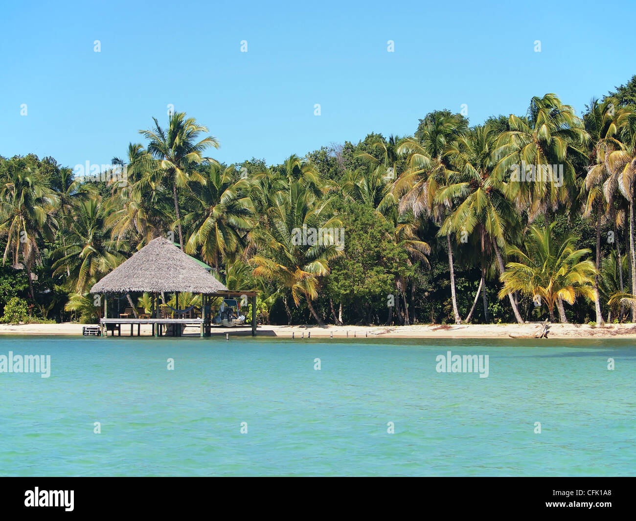 Tropical beach with thatched roof hut, Central America, Panama - Stock Image