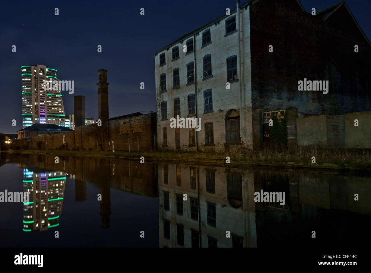Bridgewater Place (aka The Dalek) reflected in the Leeds to Liverpool canal at night - Stock Image