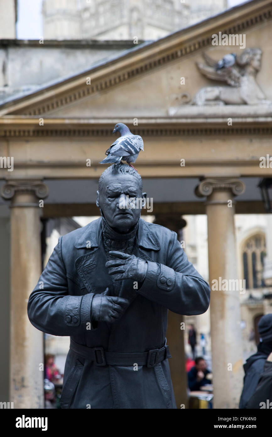 Street entertainer dressed as a statue standing still enough for a pigeon to perch on his head in Bath, Somerset - Stock Image
