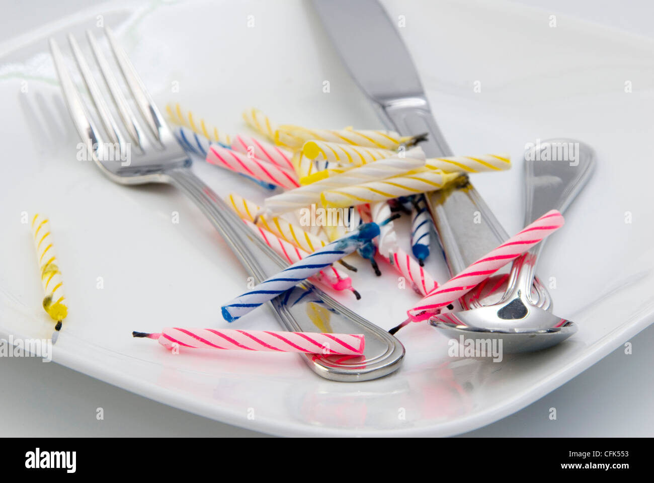 Burnt out birthday candles and utensils on plate - Stock Image