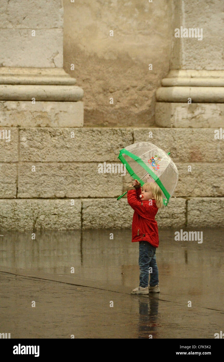 Girl in rain with umbrella and pacifier in Arco, Italy. - Stock Image