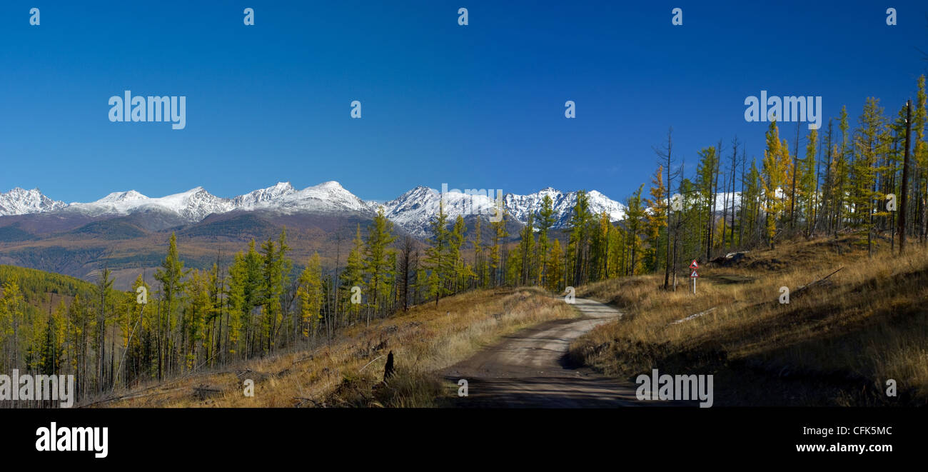 Panoramic view of snowy mountain peaks and autumnal forest valley - Stock Image