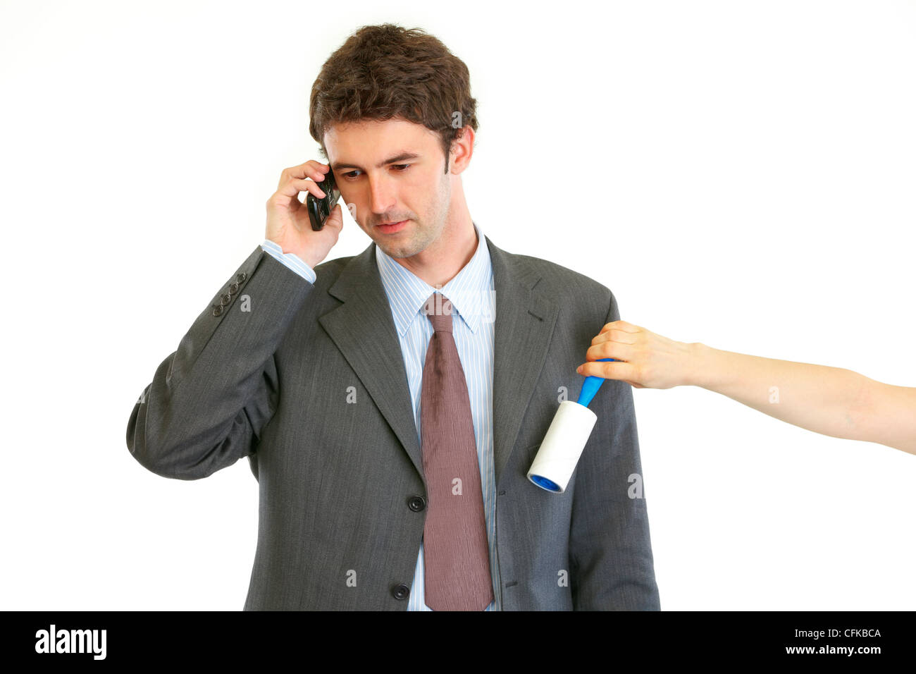 Secretary cleaning chiefs suit while he talking on phone isolated on white - Stock Image
