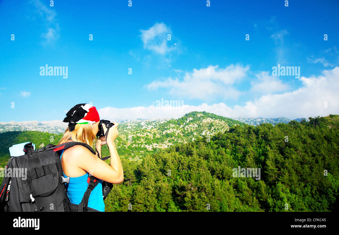 Tourist girl taking pictures of a high green mountains landscape, tourism travel vacation fun concept - Stock Image