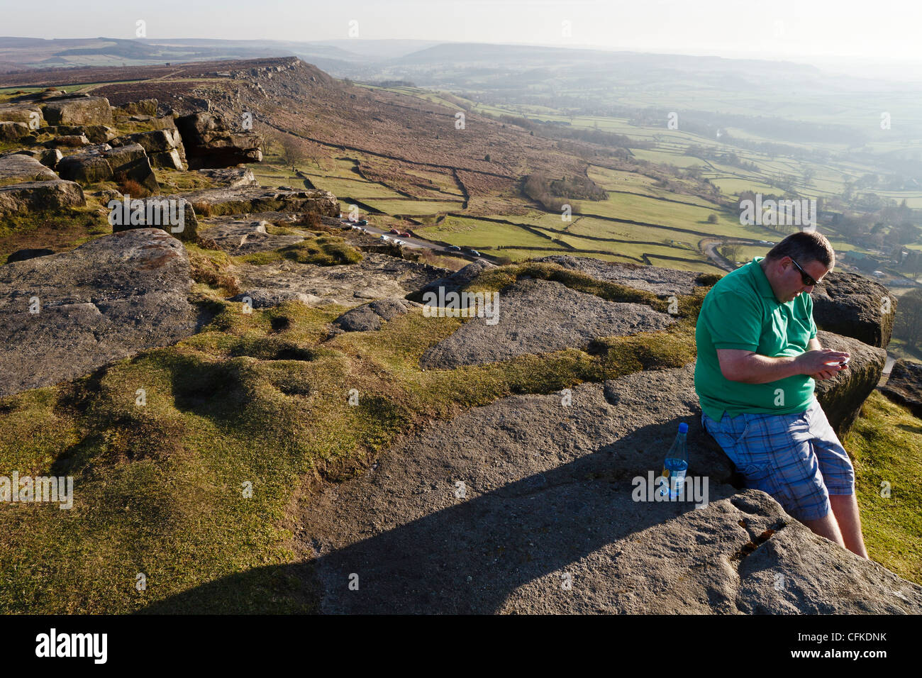 A tourist turns his back on the beautiful view to write a text message at Curbar Edge in the Peak District National - Stock Image