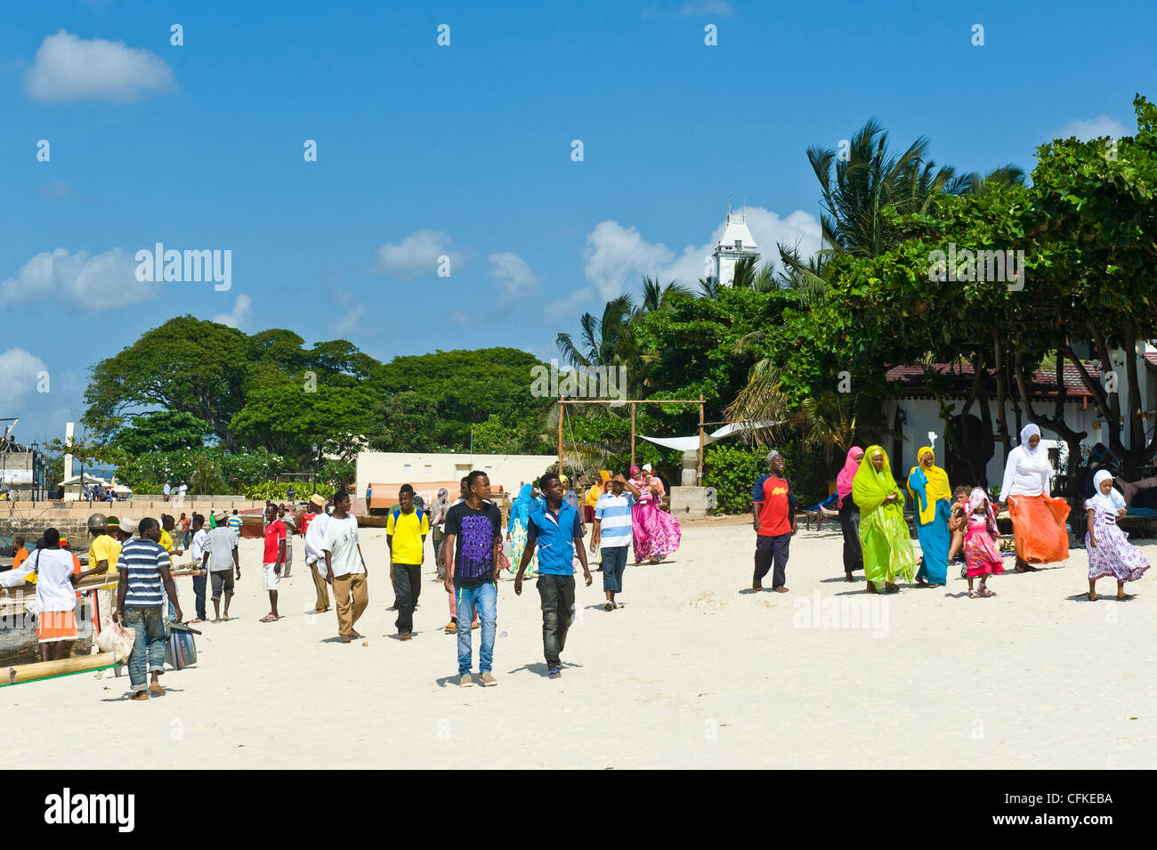 People walking along the beach in Stone Town Zanzibar Tanzania - Stock Image