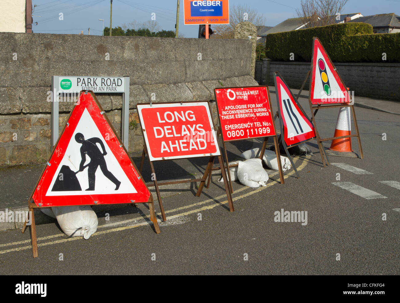 Lots of road signs while a road is dug up by a utilities company.  Camborne Cornwall UK. - Stock Image