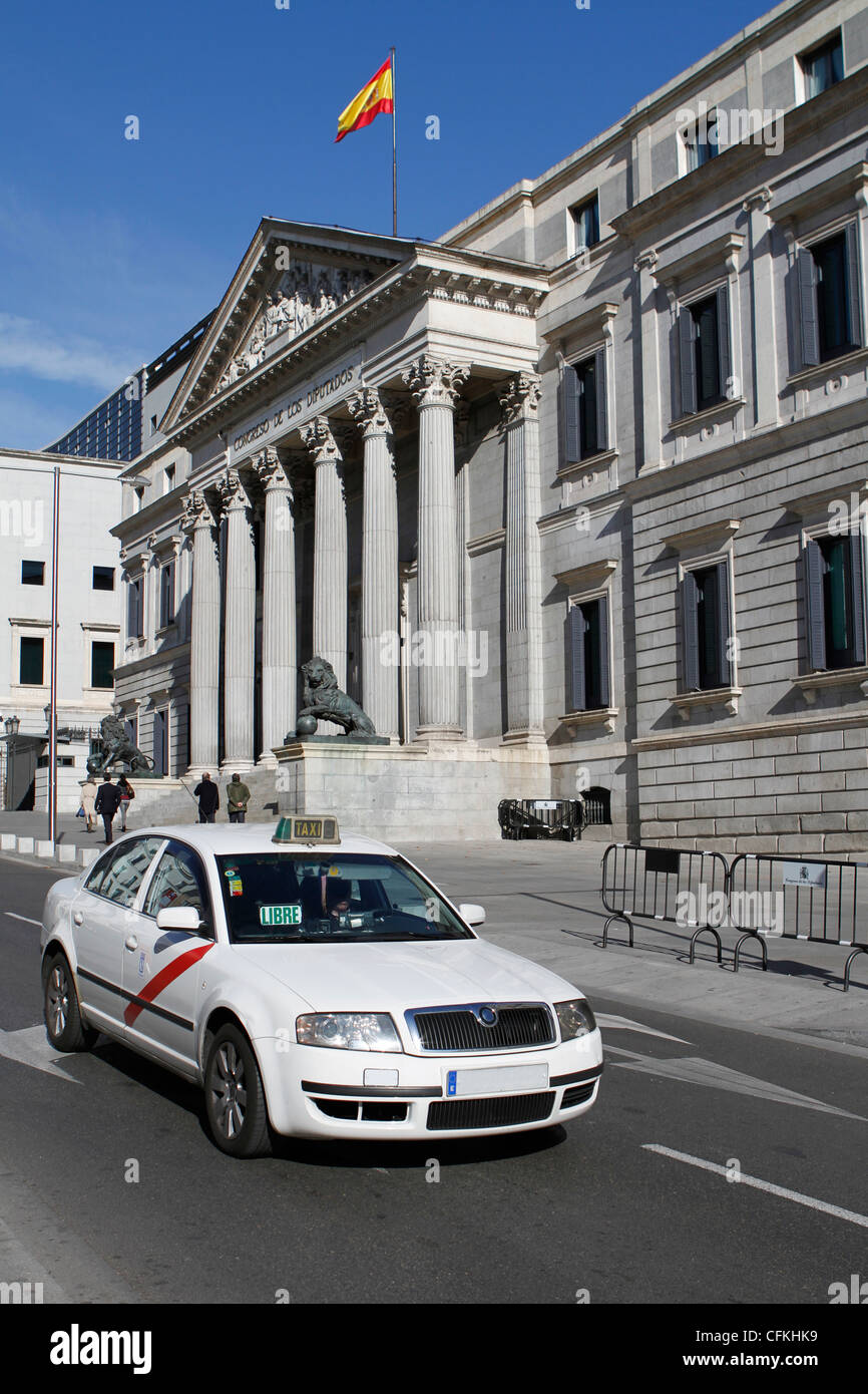 A taxicab passing by the Congreso de los Diputados building in Madrid. (Readable signs removed. People not recognizable.) - Stock Image