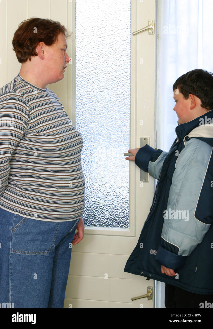 Mother talking to son in house - Stock Image