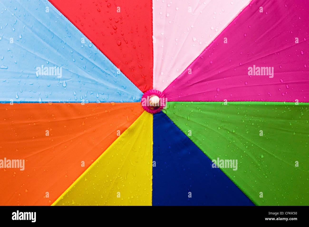 Close up of a multicoloured umbrella in the rain. - Stock Image