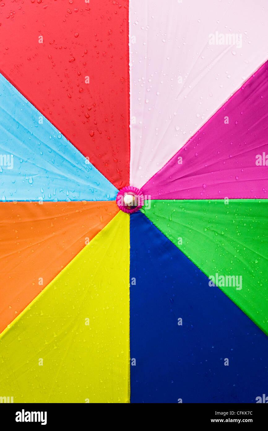 Close up of a multicoloured umbrella in the rain. Stock Photo