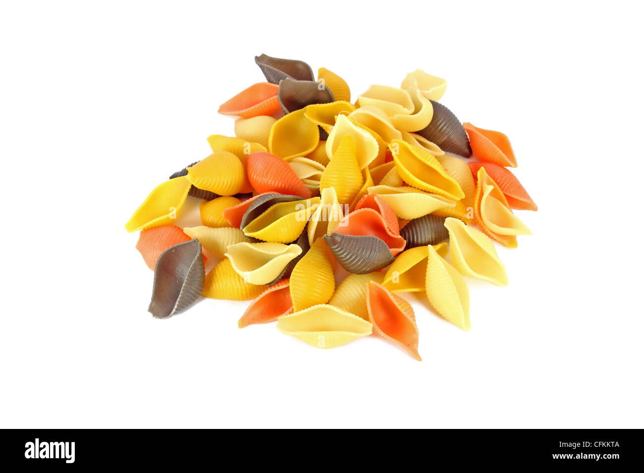 Heap of raw colored pasta shells isolated on white - Stock Image
