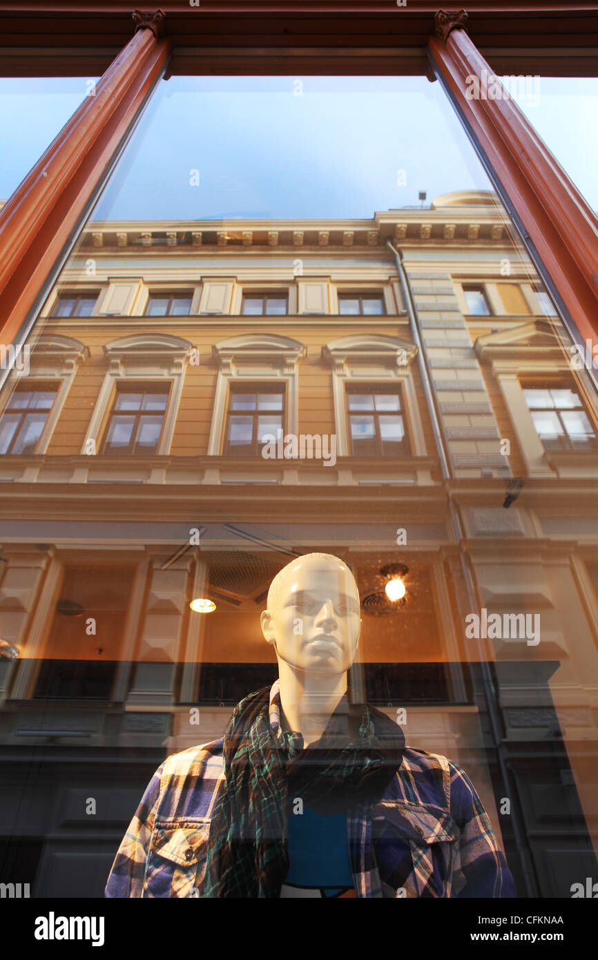 Vertical oriented image of mannequin stands behind the window with building reflection in Riga, Latvia. - Stock Image