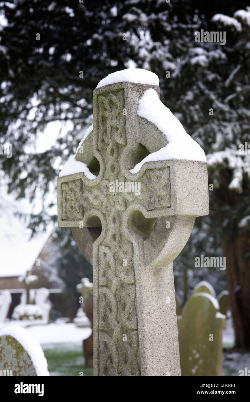 Snow lying on a headstone with a celtic pattern, in a churchyard. - Stock Image