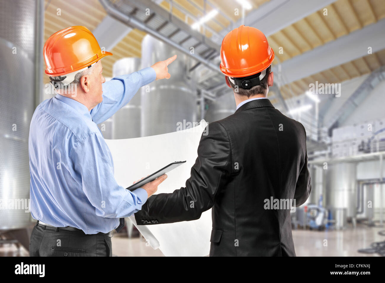 A team of construction workers with orange helmets at work place in a factory Stock Photo