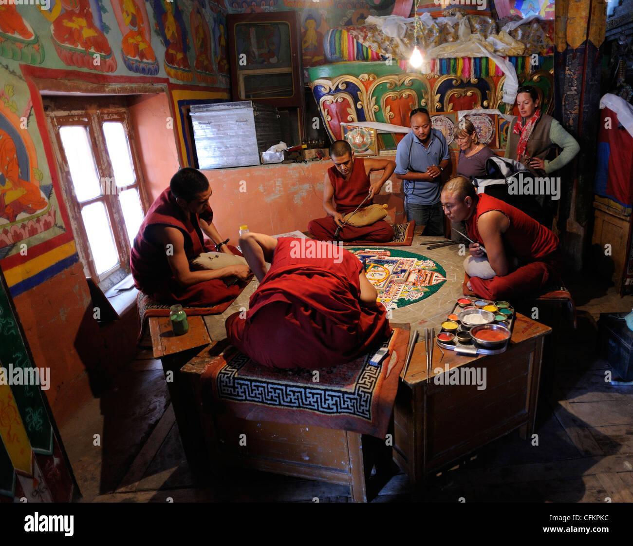 Tourists watch buddhist monks preparing a mandala using powdered pigments. - Stock Image