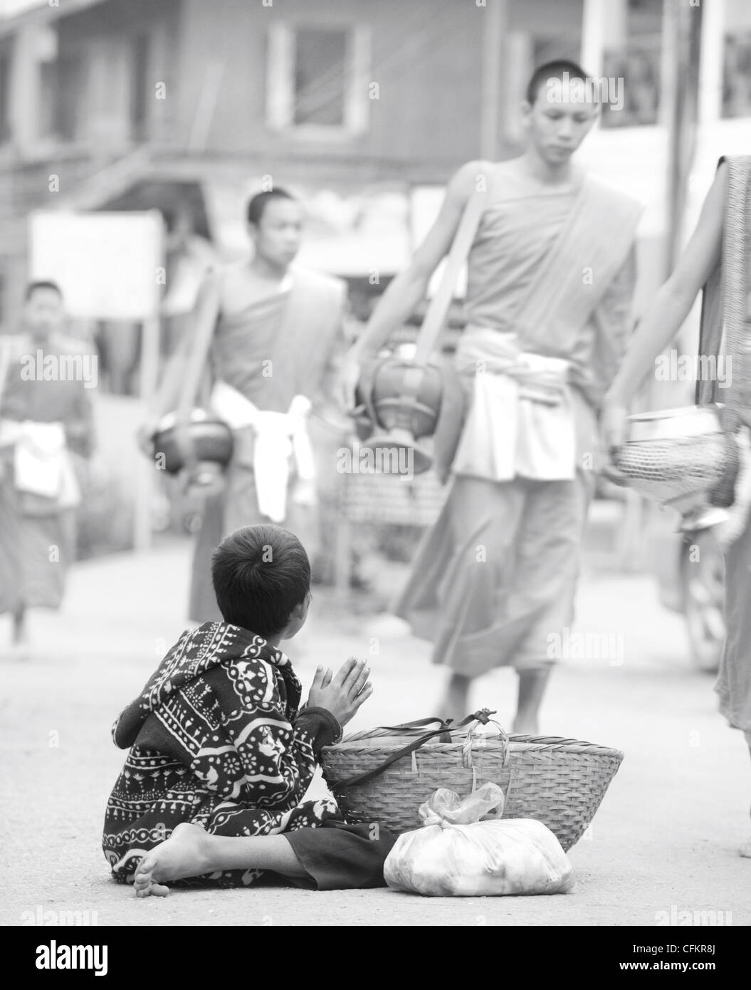 Young boy begging for food from monks who have  been given food at the daily alms giving ceremony in Luang Prabang, Stock Photo