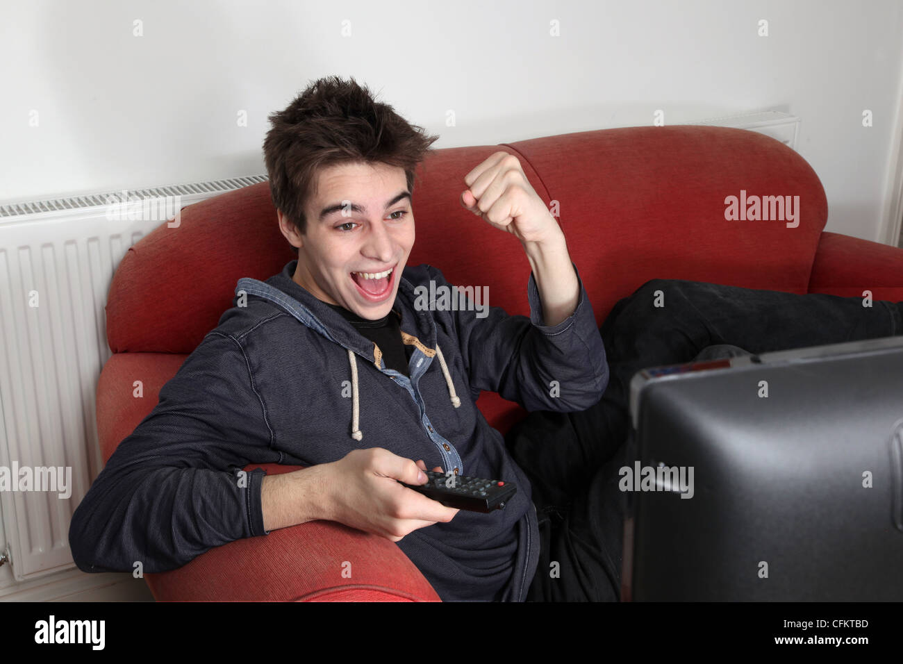 Young man watching tv alone, cheering and punching the air celebrating. - Stock Image
