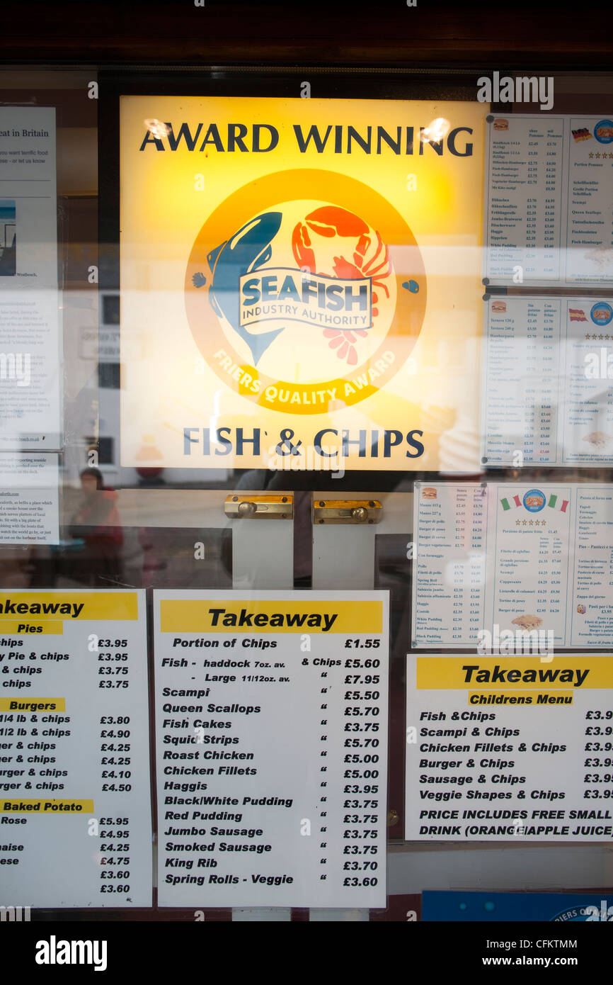 A menu in a window of a chippy selling Good old fashioned fish and chips in Ullapool Scotland - Stock Image