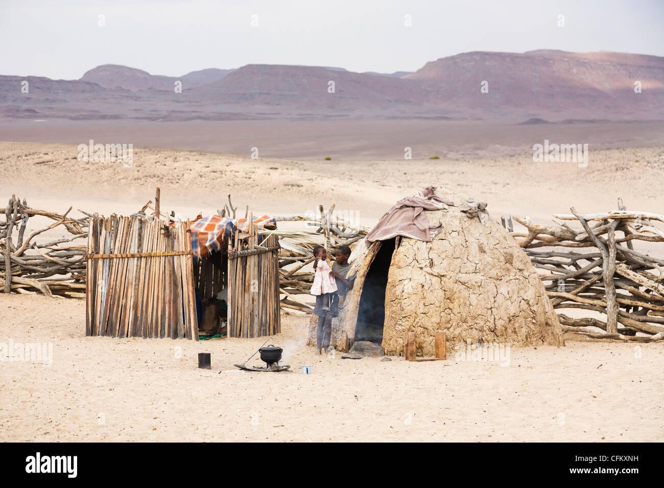 Boy holding baby girl in Himba village, Skeleton Coast, Namibia, west Africa outside mud hut within village cattle - Stock Image