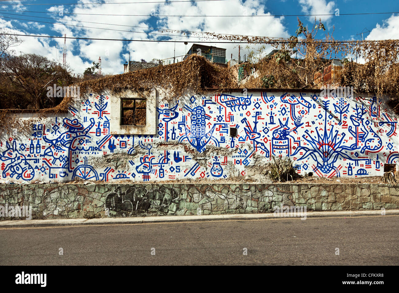 exterior wall of ruined roofless house covered with curious glyph like red white & blue geometric decorative - Stock Image