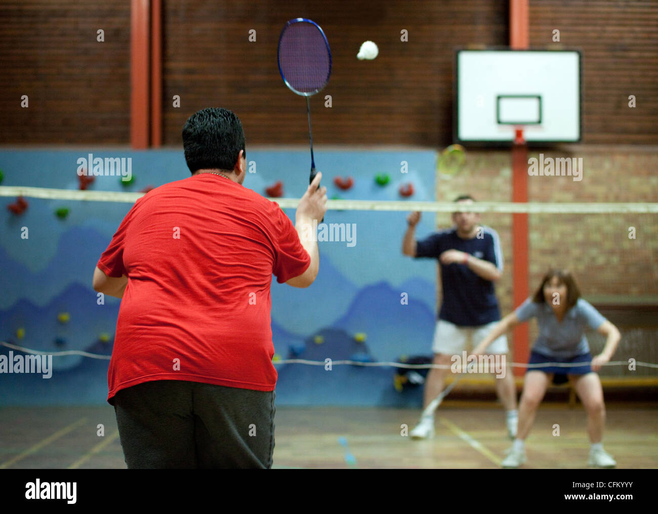 An overweight man playing badminton for exercise, UK - Stock Image
