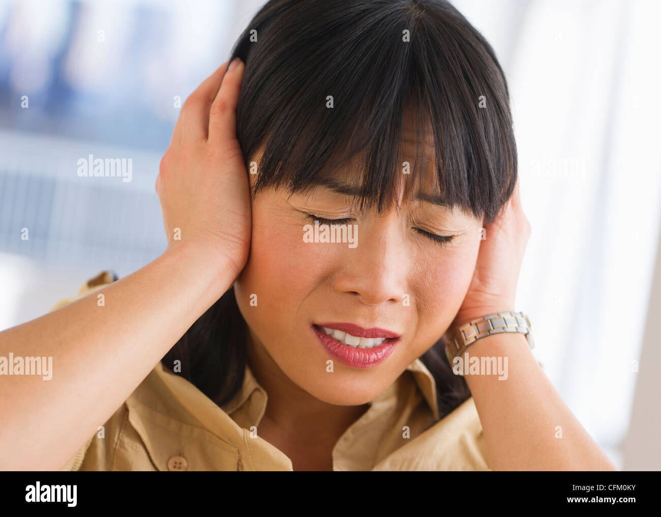 USA, New Jersey, Jersey City, Woman covering ears - Stock Image