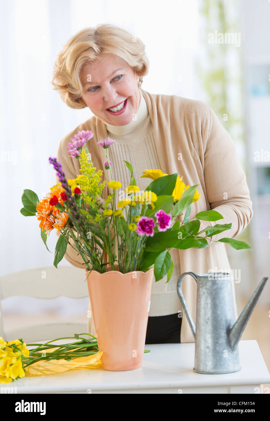 USA, New Jersey, Jersey City, Smiling senior woman arranging flowers Stock Photo