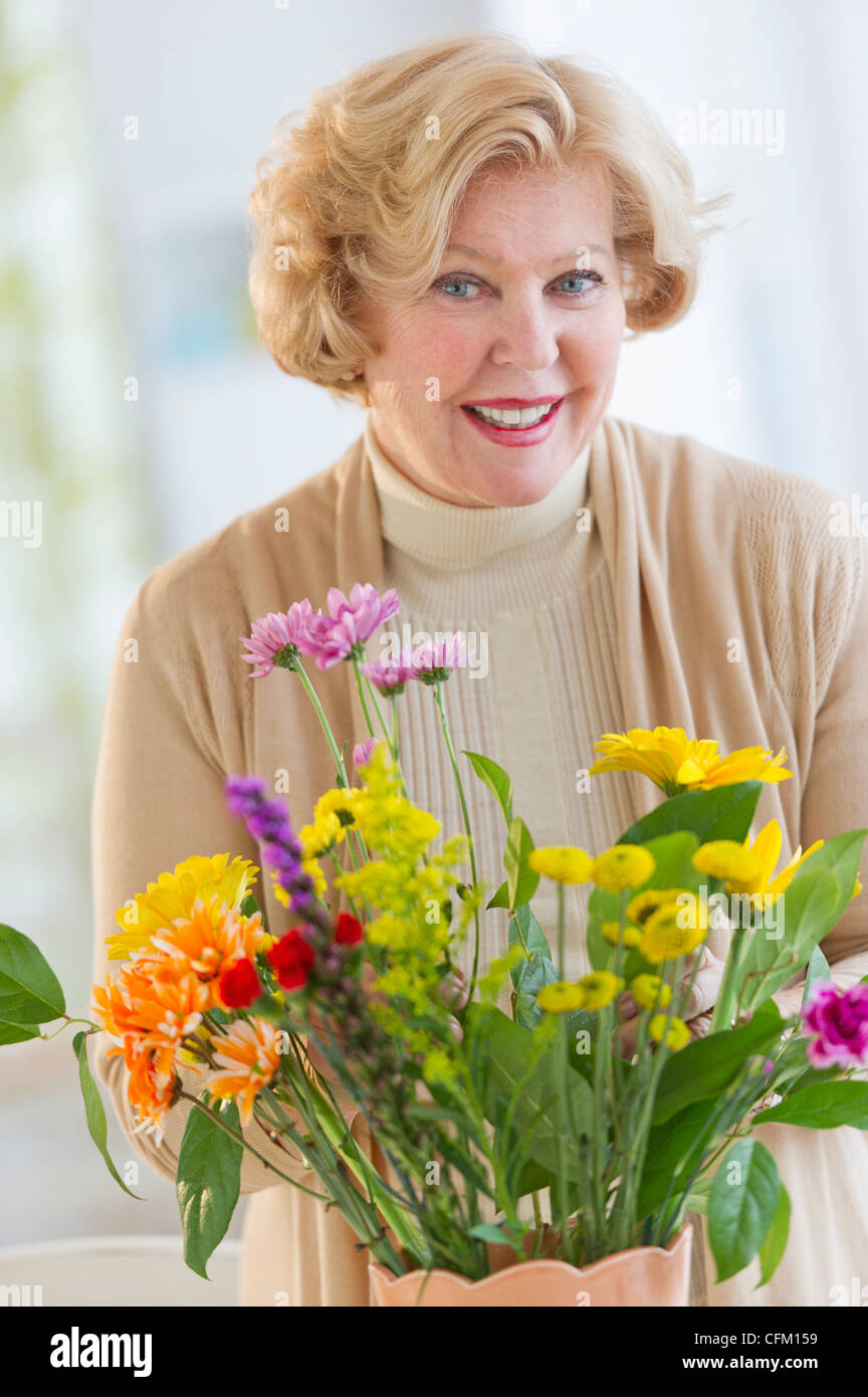 USA, New Jersey, Jersey City, Smiling senior woman arranging flowers Stock Photo