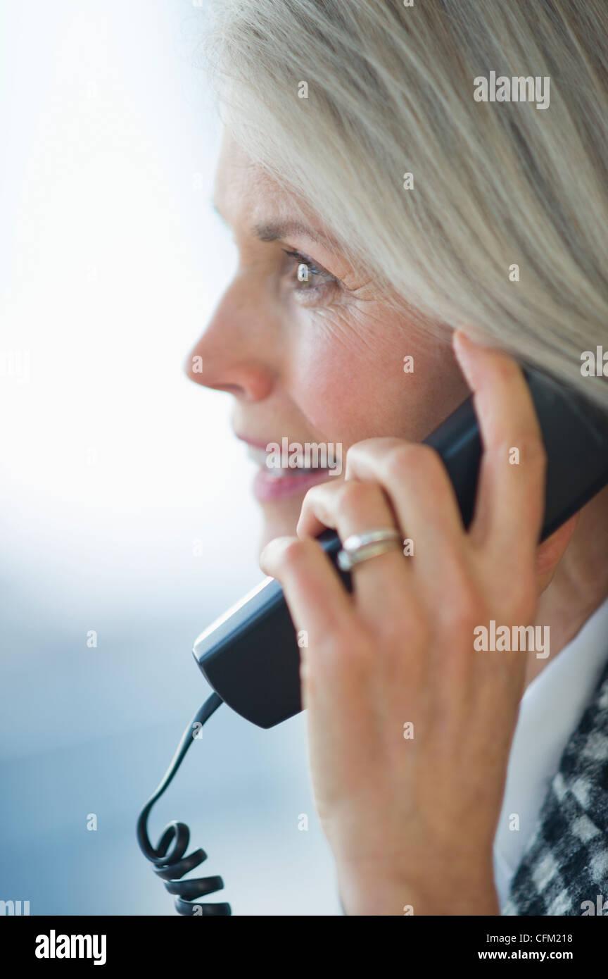 USA, New Jersey, Jersey City, Portrait of senior businesswoman talking on phone - Stock Image