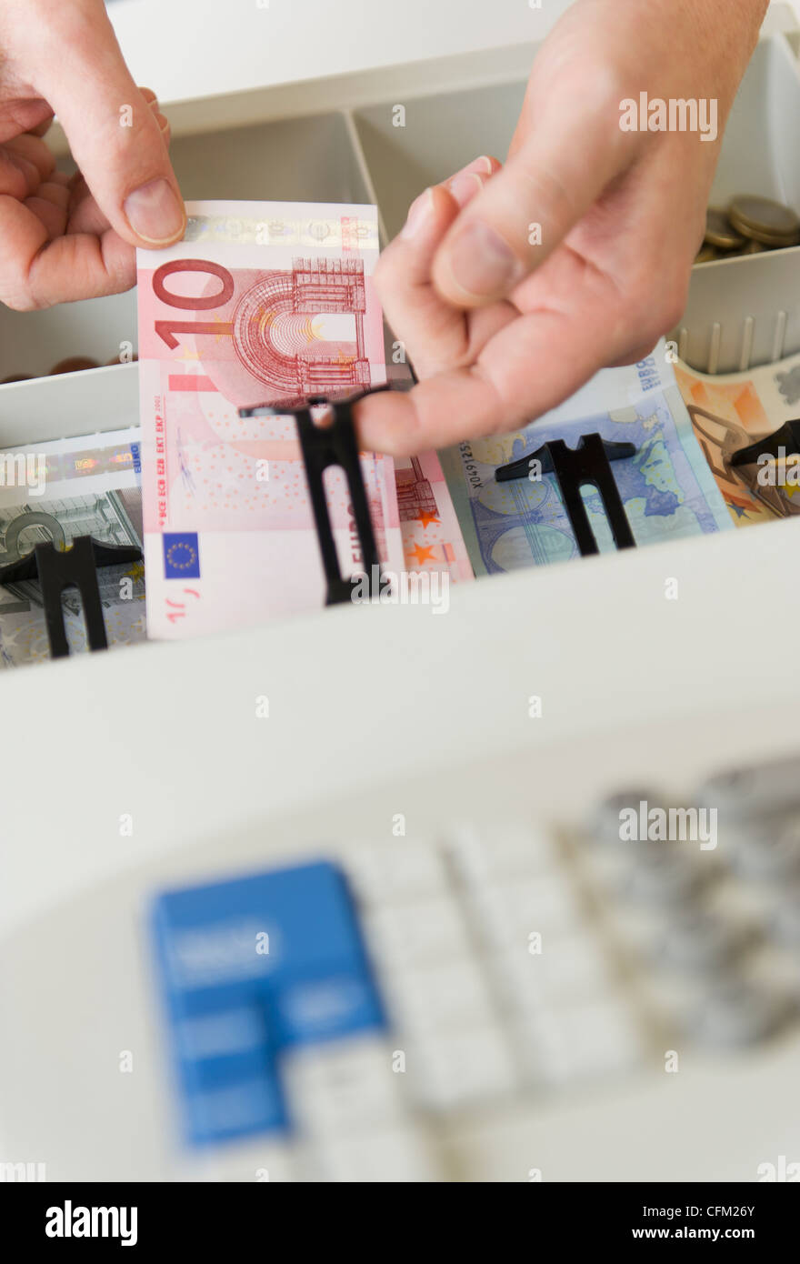 Close up of man's hand putting banknotes into cash register, studio shot - Stock Image