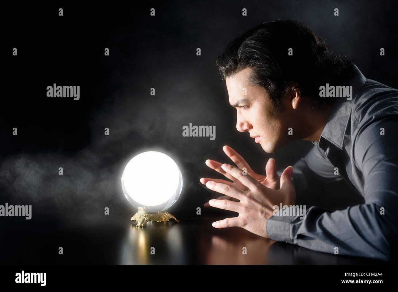 Studio shot of businessman looking at crystal ball - Stock Image