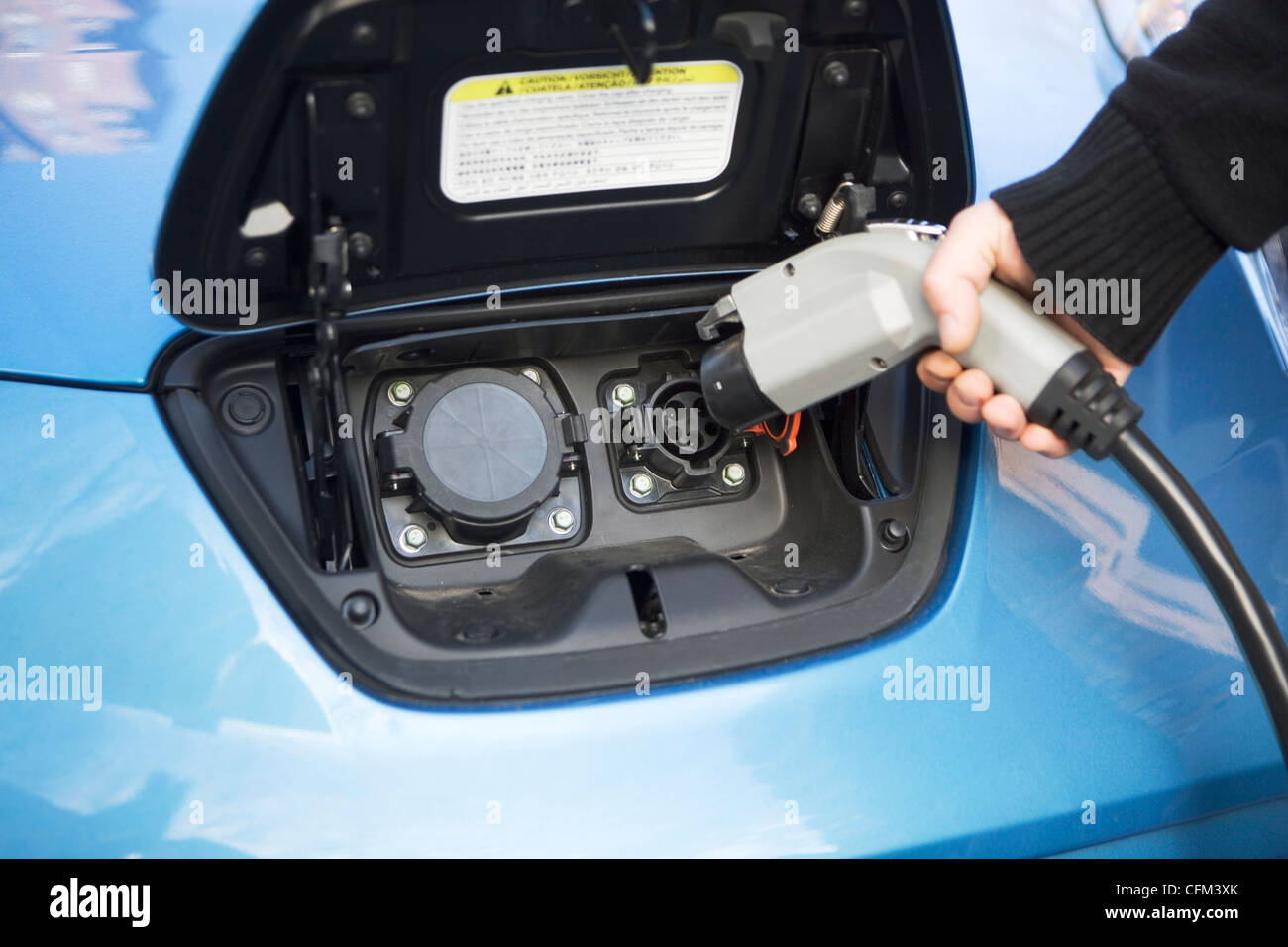 USA, New York State, New York City, close-up of man charging electric car - Stock Image