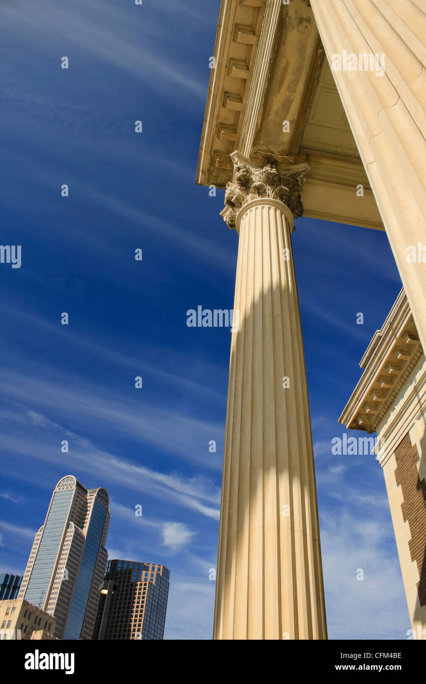 Corinthian columns with modern buildings in the background, shot against a deep blue sky. - Stock Image