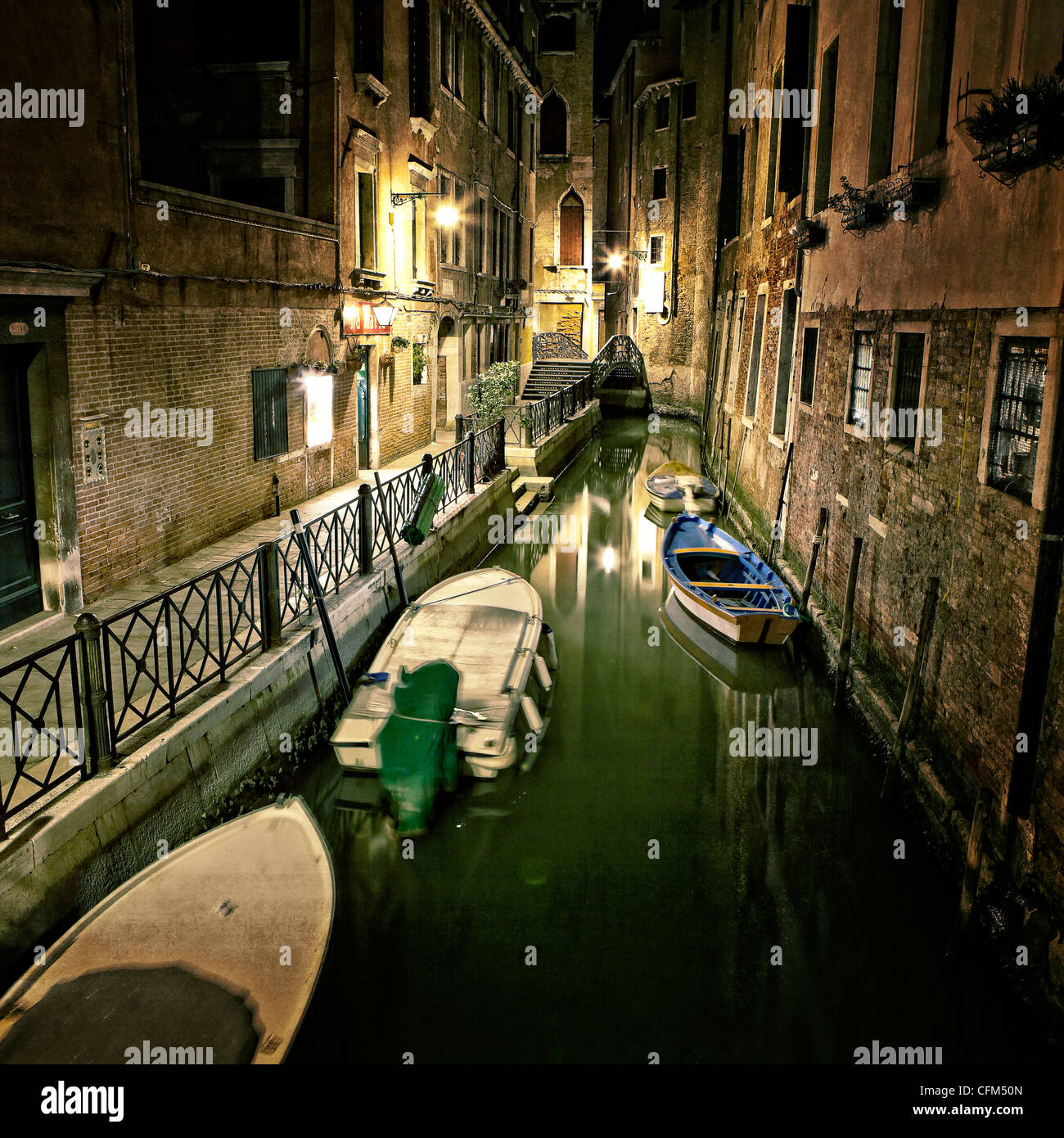 narrow canal in Venice with boats moored - Stock Image