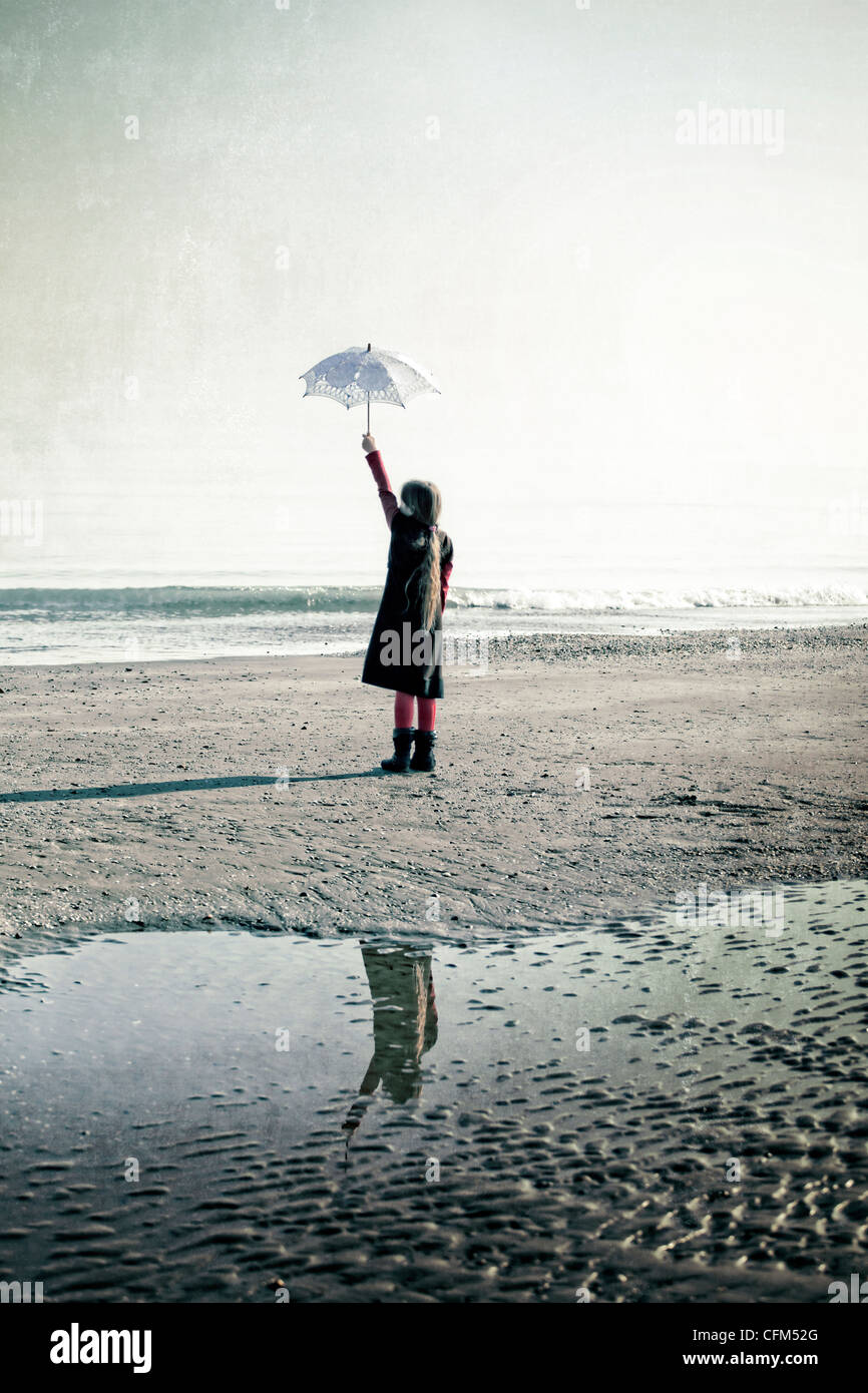 Girl on the beach with parasol - Stock Image