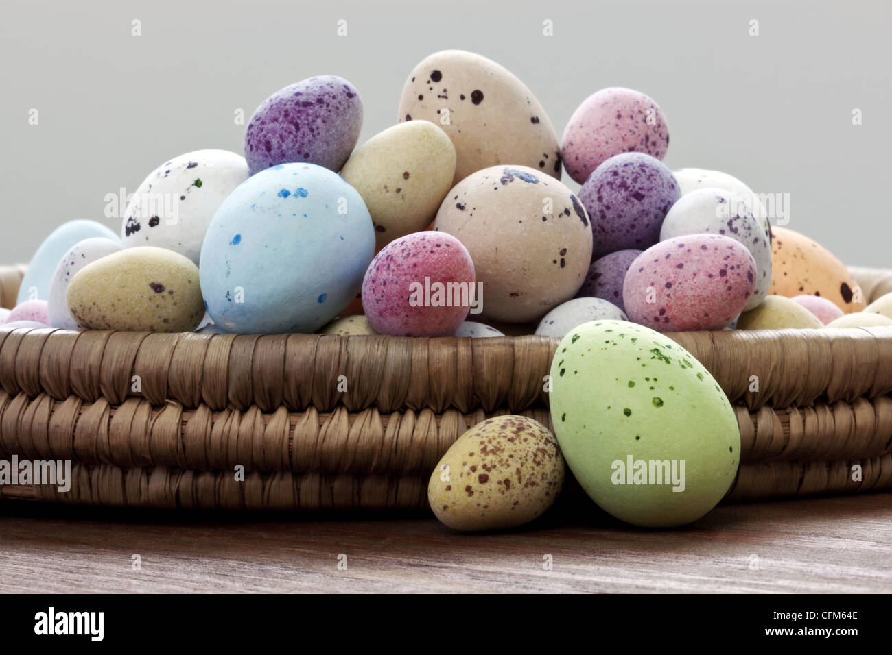 Still life photo of speckled candy covered chocolate easter eggs in a wicker basket on a rustic wooden table. - Stock Image
