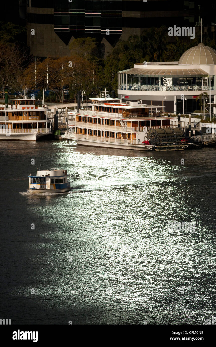 Paddle steamers at Eagle Street Pier and ferry boat on Brisbane River in city centre, Brisbane, Queensland, Australia, - Stock Image