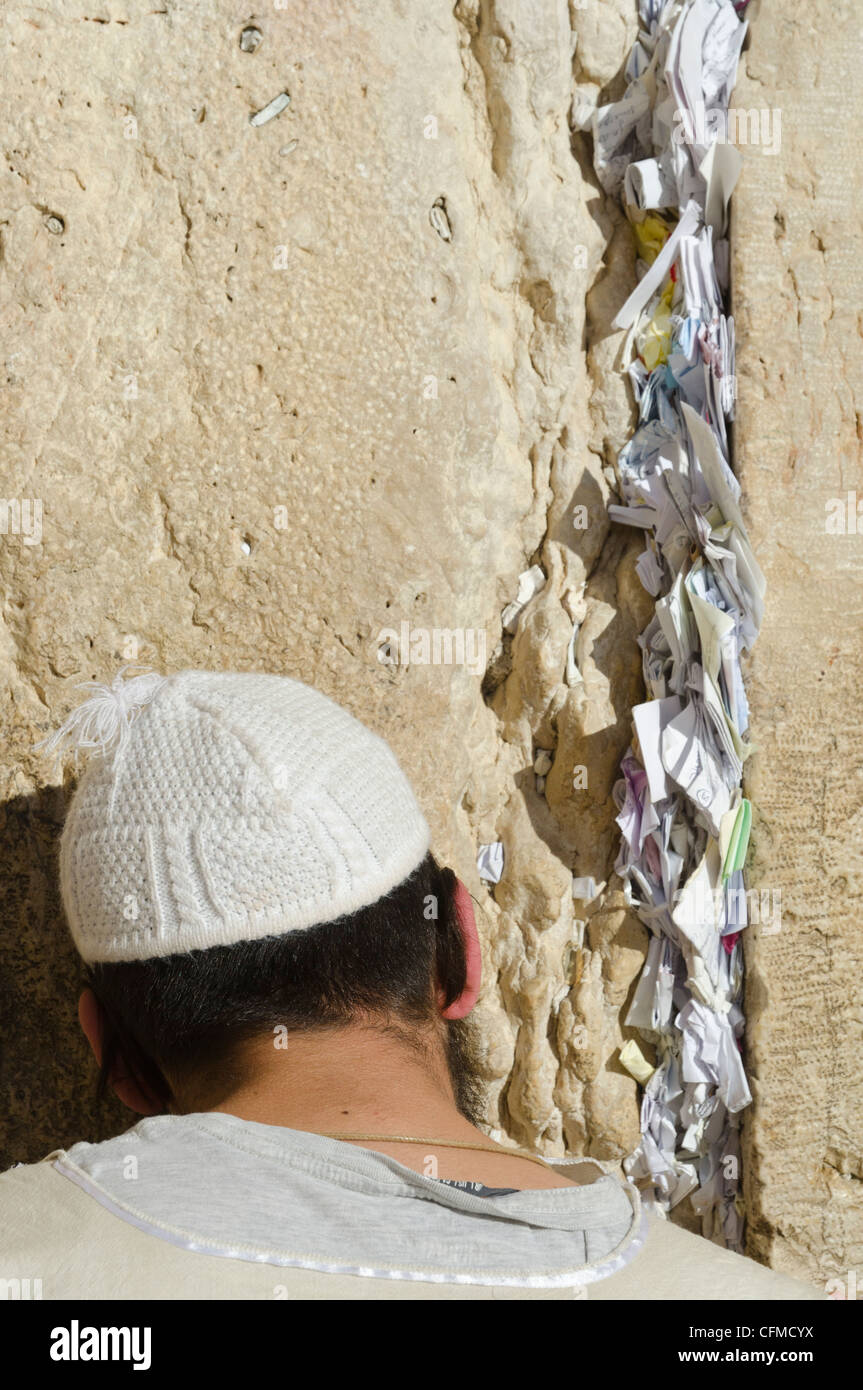 Orthodox Jew praying at Western Wall, with paper notes in crack, Old City, Jerusalem, Israel, Middle East - Stock Image
