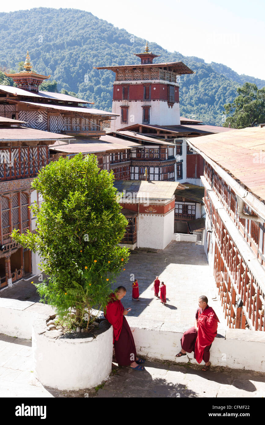 View over the main courtyard of Trongsa Dzong with Buddhish monks chatting, Trongsa, Bhutan, Asia - Stock Image