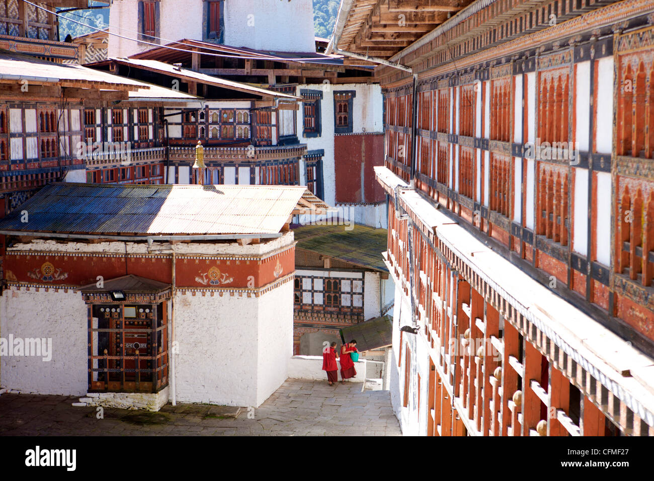 Two Buddhist monks chatting against the imposing backdrop of Trongsa Dzong, Trongsa, Bhutan, Asia - Stock Image
