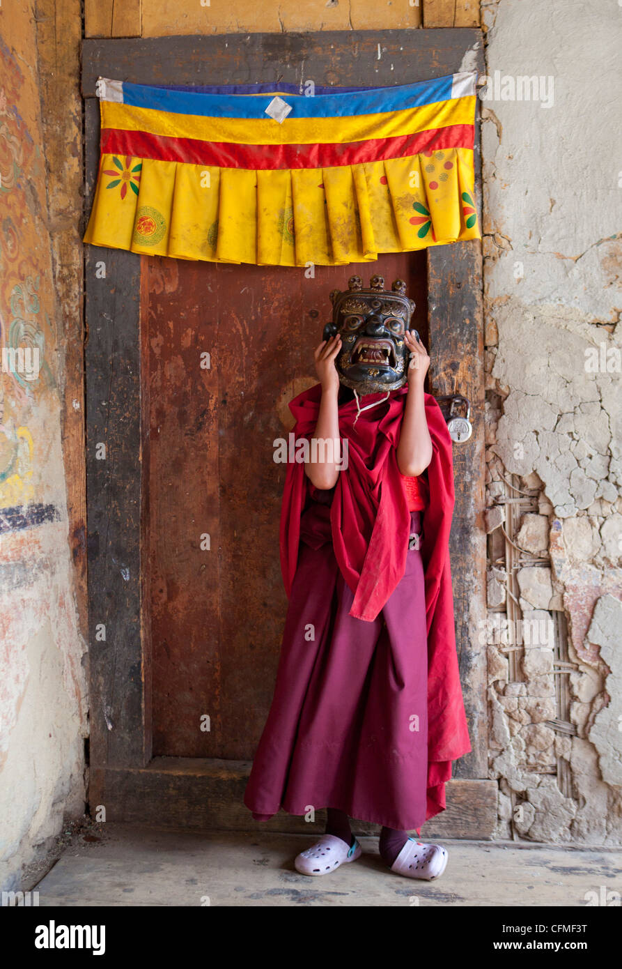 Young Buddhist holding holding carved wooden mask, Jakar, Bumthang, Bhutan, Asia - Stock Image
