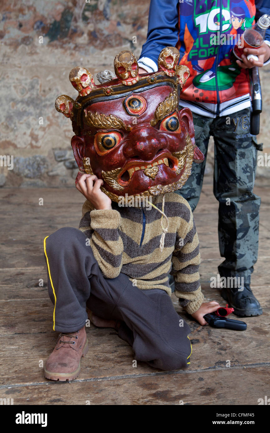 Young boy holding large carved wooden mask to his face at the Tamshing Phala Choepa Tsechu, near Jakar, Bumthang, - Stock Image