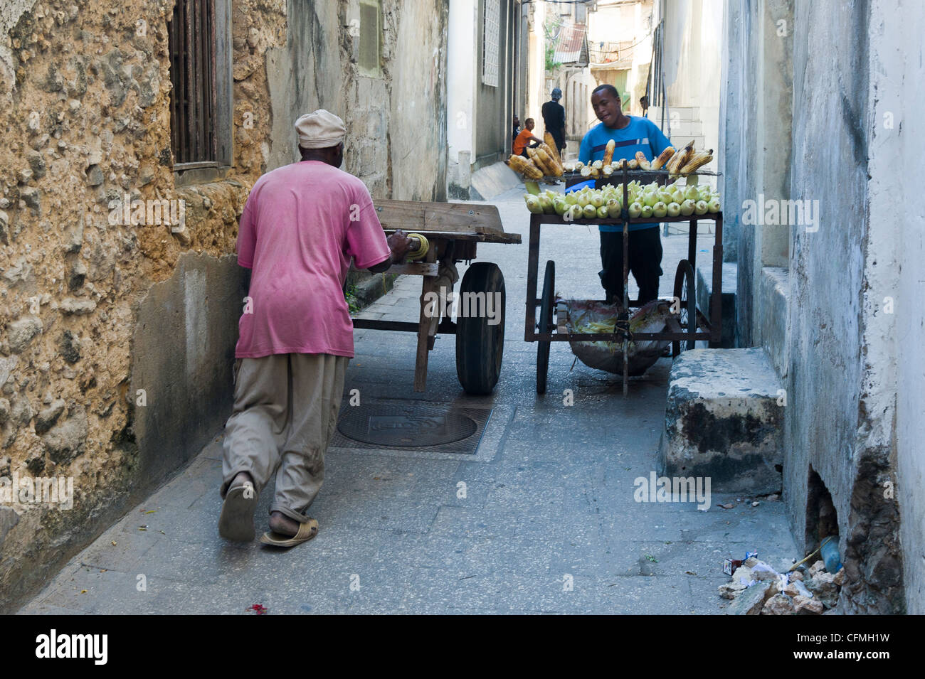 Men pushing carts through the narrow alleys of Stone Town Zanzibar Tanzania - Stock Image