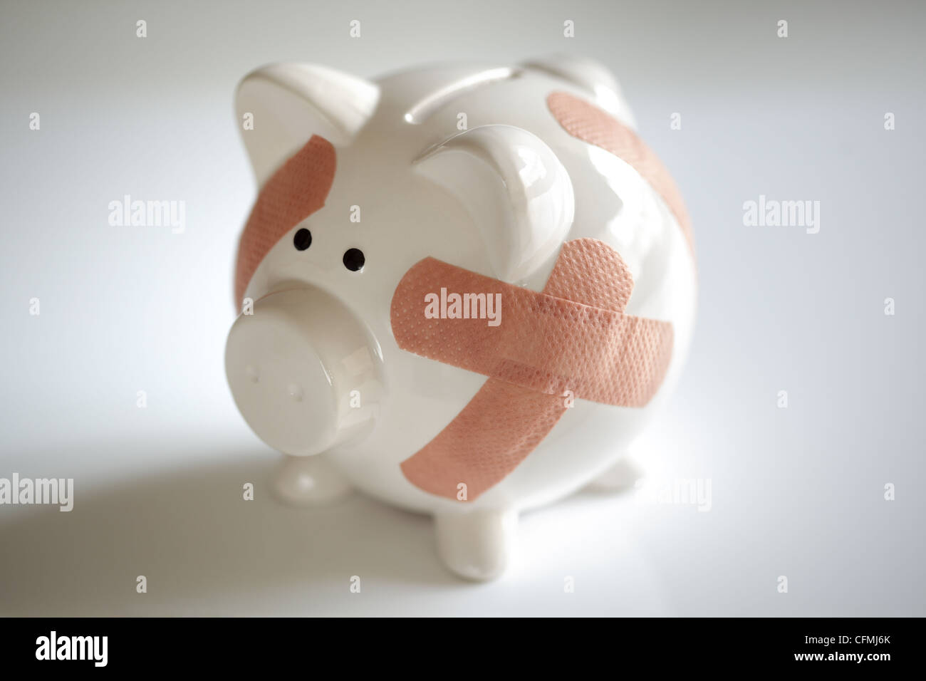 Piggy bank with band aids - Stock Image