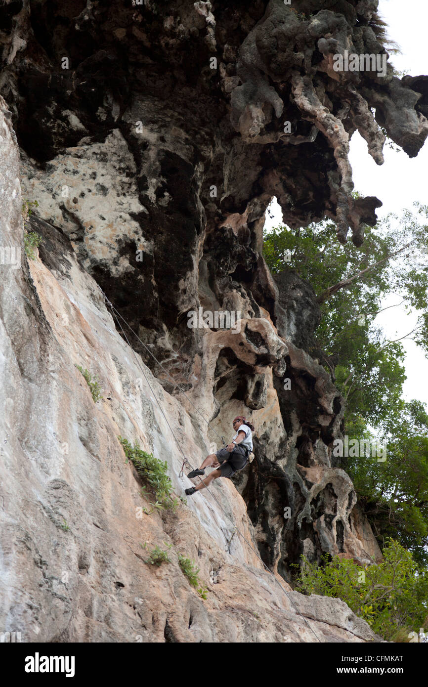 After demonstration, a Thai instructor of rock climbing ropes down (East Railay - Krabi - Thailand)  Instructeur Stock Photo
